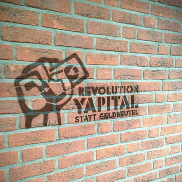 Yapital revolution graffiti on a wall guerilla marketing